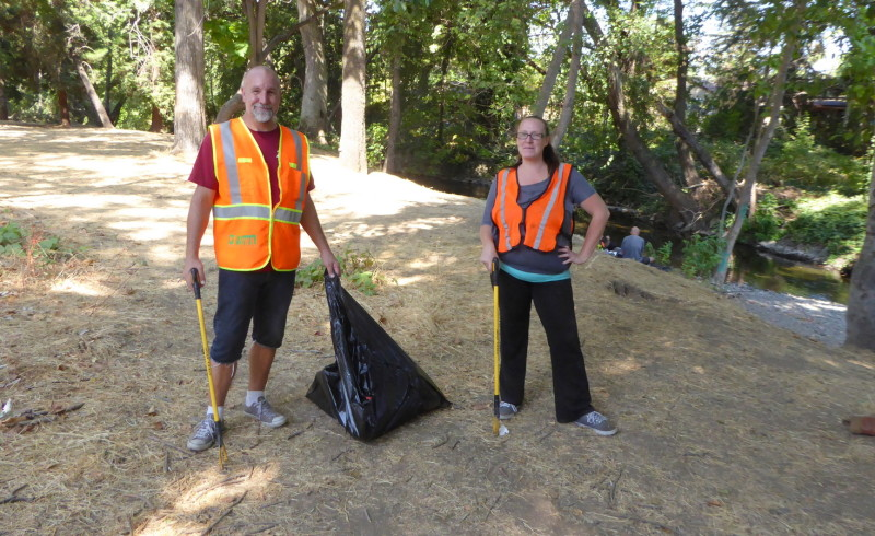 Two members of the DCBA clean-up brigarde posing for the camera at Lost Park wearing orange vests for visibility and equipped with a trash bag and trash grabbers